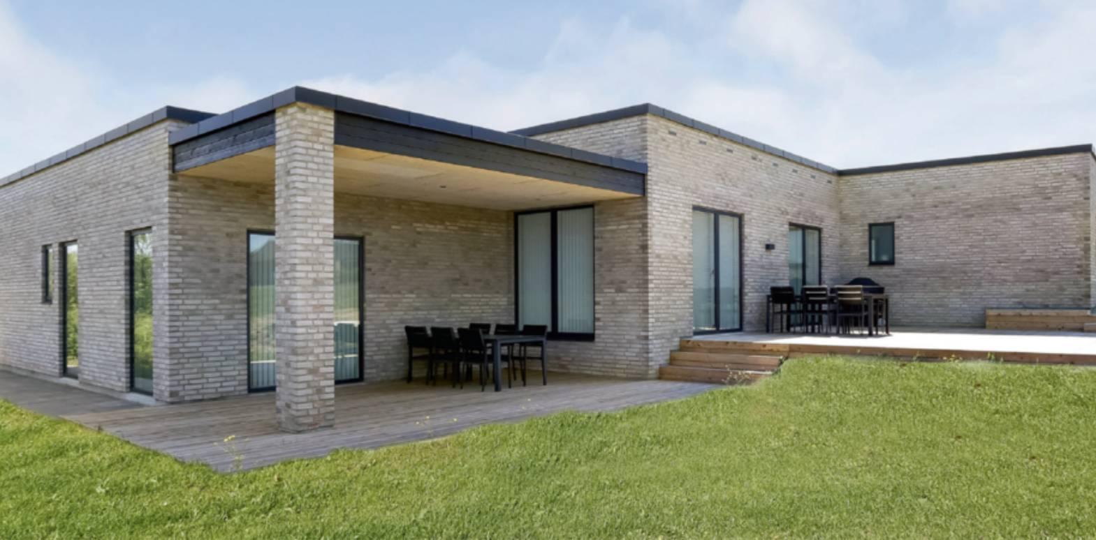 Hus i sandfarvede musrten af typen funkis som man kan overveje når man skal byg nyt hus